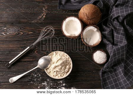 Coconut flour in ceramic bowl on wooden table