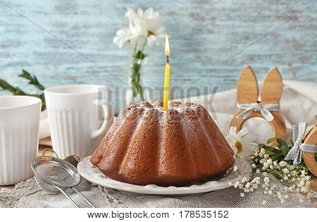 Plate with Easter cake and votive candle on wooden table