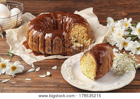 Plate with slice of delicious Easter cake on wooden background