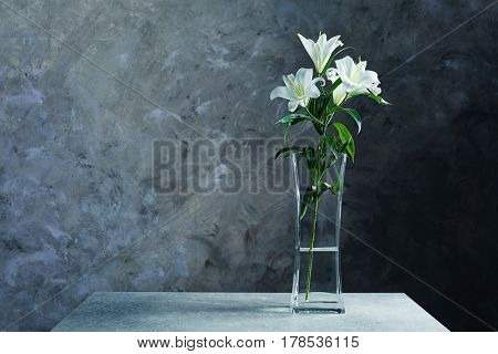 Beautiful white lilies in vase on table