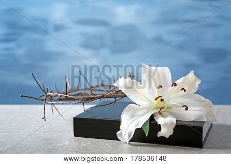 Holy Bible, crown of thorns and white lily on light background