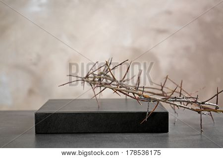 Crown of thorns and Holy Bible on beige background
