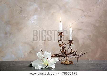 Crown of thorns, lily and candles on beige background