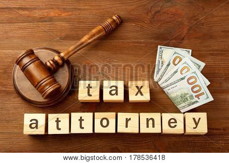 Wooden cubes with space for text, gavel and dollar banknotes on table. Tax attorney concept