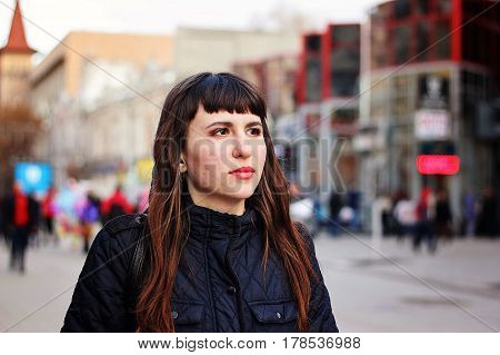 Portrait of a beautiful dreamy girl on a central city street.