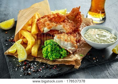 British Traditional Fish and chips with mashed peas, tartar sauce on crumpled paper with cold beer