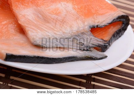 fresh salmon fillet close up on white plate