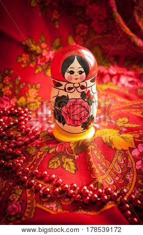 Matryoshka on a background of red patterned headscarf