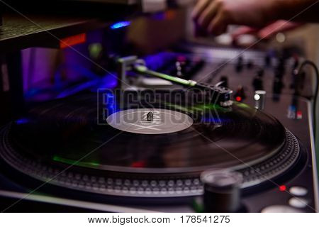 Turntable Playing Vinyl Close Up With Needle On The Record And Playing Dj On The Background. Selecti