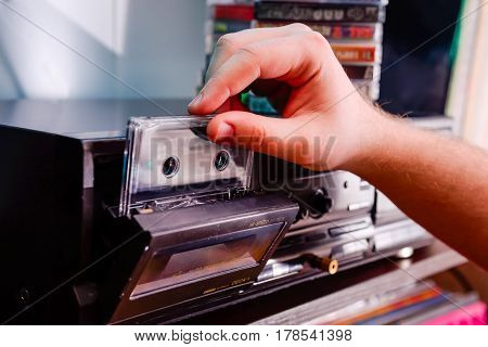 Close Up Man's Hand Put Cd Cassette Into Old Fashioned Cd Audio Player. Selective Focus