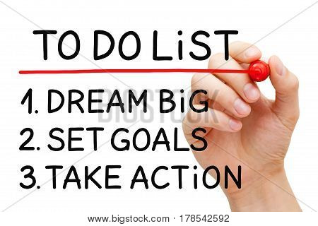 Hand writing Dream Big Set Goals Take Action in to do list with marker on transparent wipe board.