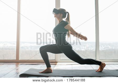 A young beautiful girl in virtual reality glasses makes yoga and aerobics remotely. Future technology concept. Modern imaging technology. Classes in single sports remotely.