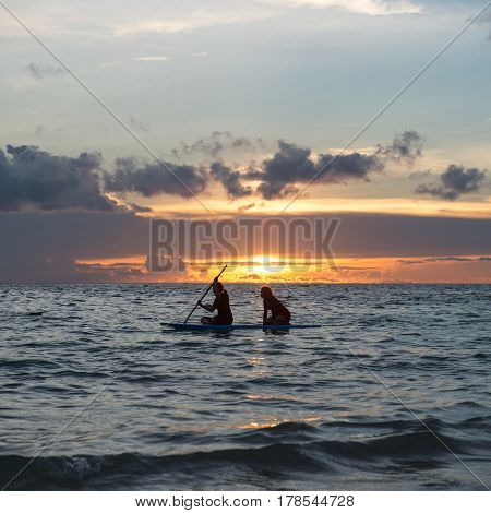 Two girls sits on paddle boarding on quiet sea at sunset