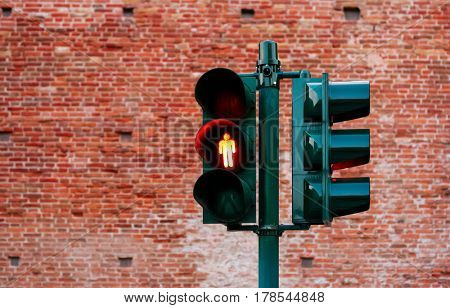 Green traffic light with burning yellow lamp supervisory road. Transport street routes management object for city crossroads, on the brick wall background.