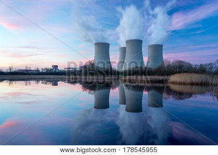 Nuclear power plant after sunset. Dusk landscape with big chimneys.