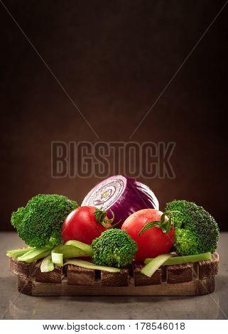 Concept design image for a cookbook or magazine cover vegetables on a wooden platter on a dark background
