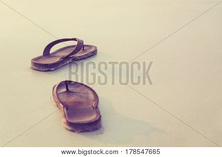 Abstract brown shoes on beach with sand background vacation and holiday concept with copy space