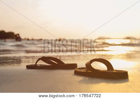 Abstract brown shoes on beach and sand with sunset background vacation and holiday concept with copy space