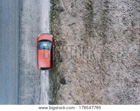 Red car on country road in spring time. Aerial view.