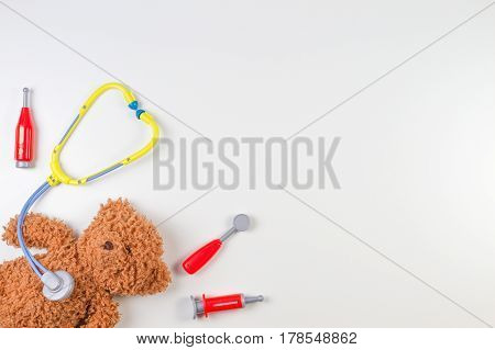Teddy bear with toy stethoscope and toy medicine tools on a white background. Top view. Copy space for text