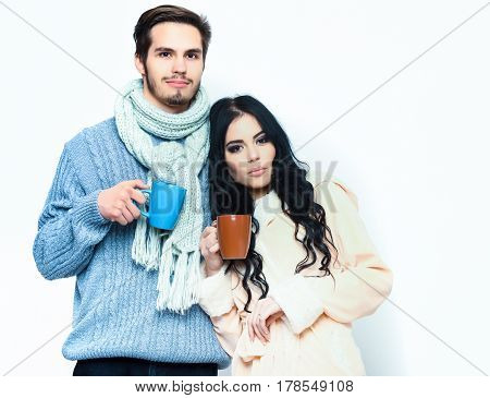 lovely cute happy couple holding colorful cups. Bearded caucasian man with moustache in knitted blue sweater and scarf with brunette pretty girl in beige robe drink coffee isolated on white
