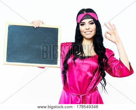 pretty cute happy sexy girl or beautiful smiling woman with fashion makeup and long black hair in pink or fuchsia silk robe with bandage on head holding black board and showing ok isolated on white