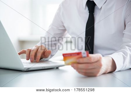 Businessman holding credit card and using laptop. Online payd.