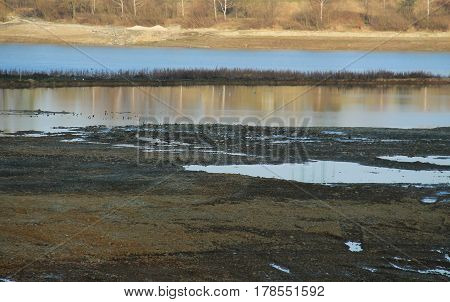 drying dam Olesna with partly revealed boggy bottom and reflections on the calm surface, Czech Republic