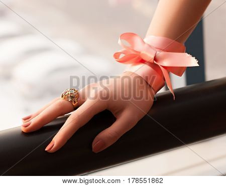 The Girl Puts A Hand On The Handrail. On The Hand Ring And A Pink Bow On The Wrist.