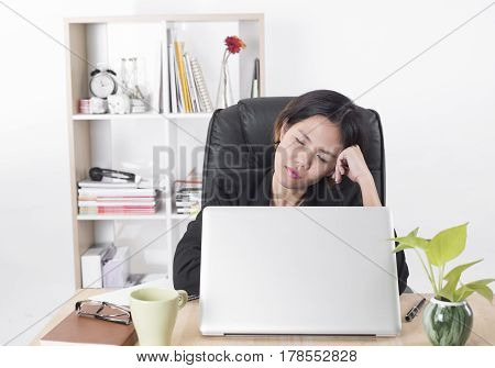 Businesswomen working at office desk.she feels bored and tried job on laptop. sleep concept.