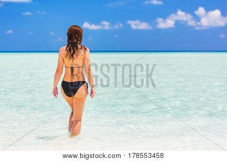 Attractive young woman enjoys Maldivian beach walking in the ocean water