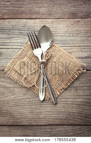 Old fork and spoon on a wooden table napkin and burlap, grunge rustic style, top view.
