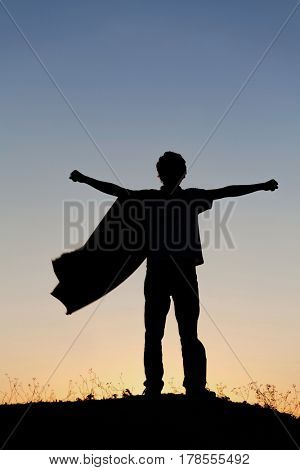 Boy playing superheroes on the sky background, silhouette of teenage superhero in a red cloak on a hill