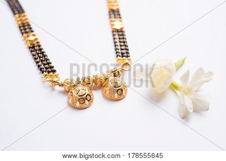 close-up photo of a Mangalsutra or necklace to worn by a married hindu women, with huldi kumkum and mogra flowers or Jasminum sambac garland over white background