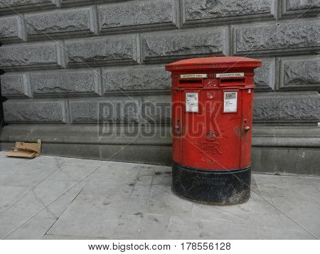 Traditional red mailbox with grey stone wall .