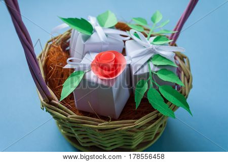 White Gifts In A Basket With Paper Flower On Blue Background