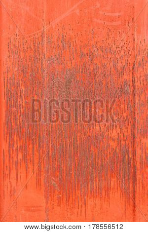 Texture of rusty worn metal under red paint