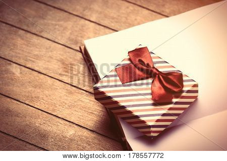 photo of cute gift on the opened notebook on the wonderful brown wooden background