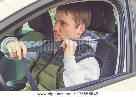 Young Man Fasten Safety Belt. Safe Driving