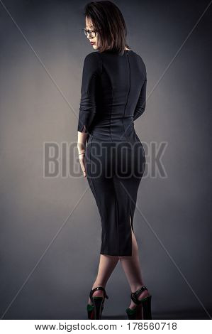 elegant young girl in dress isolated on gray background
