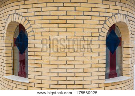 Closeup of round beige brick wall of a chirch with arched windows with image of cross