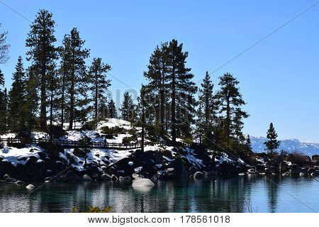 This image is taken at Tahoe and has a little bit of everything from trees to the lake to some snow!