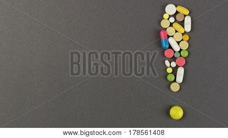 Exclamation point created from colored pills. Medical concept.