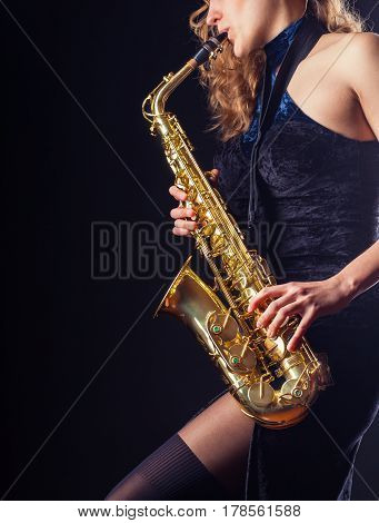 Saxophone player. Woman with saxophone on a dark background