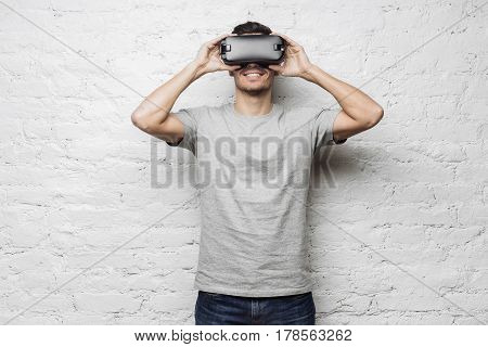 Technology gaming and people concept. Young attractive caucasian man wearing grey t-shirt and virtual reality headset or 3d glasses playing video game or watching movie against white brick wall