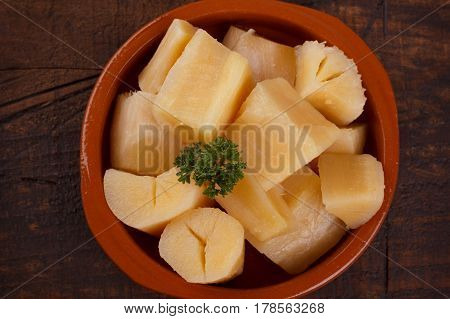 Cooked manihot esculenta (cassava, yuca, manioc, mandioca, Brazilian arrowroot) -  woody shrub on wooden background. Selective focus