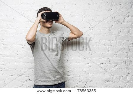 Technology science innovation and cyberspace concept. Portrait of young attractive caucasian male wearing vr goggles. White man experiencing virtual reality using 3d headset against white brick wall