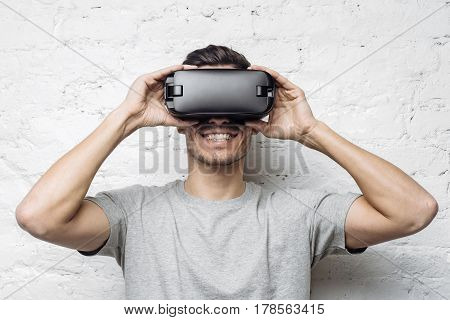 Close up portrait of handsome man playing video games in goggles or 3d glasses. European player wearing virtual reality headset for smart phone on his head smiling standing against white brick wall