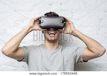 Astonished handsome guy in gray t-shirt experiencing virtual reality while using oculus rift headset for entertaining standing against white brick wall. People technology and innovation concept.