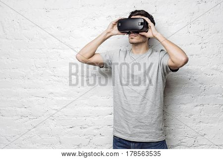 Calm and confident handsome caucasian man in casual gray t-shirt holding hands on goggles using oculus rift headset experiencing virtual reality while standing against white brick wall. VR concept